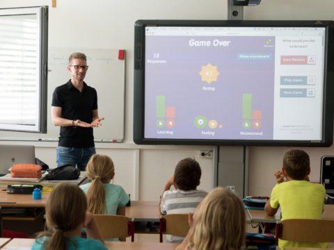 Lehrer unterrichtet mithilfe einer interaktiven Tafel